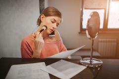 Busy woman making a make-up, talking on the phone, reading documents t the same time. Businesswoman doing multiple tasks royalty free stock images