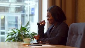 African american businesswoman working with laptop and papers. Busy woman paying bills online banking managing finances