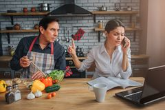 Busy woman sit at table and talk on phone. Man look and lean to her. They sit at table in kitchen. Guy interrupt woman. Busy women sit at table and talk on phone stock photography