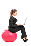 Busy woman sitting on ball and working on laptop Stock Photos