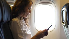 Busy woman with smartphone in airplane. Sitting near window. Businesswoman working in airliner, texting message in phone stock video footage