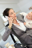 Busy woman talking on the phone and carrying her baby Royalty Free Stock Photography