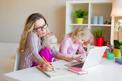 Busy woman trying to work while babysitting two kids. Busy women trying to work while babysitting two kids at home stock images