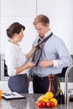 Busy woman tying husband's tie Stock Photo