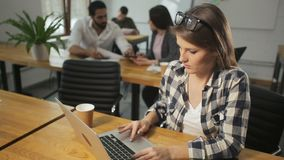 Busy Woman Typing on Computer. Busy long-haired woman typing on the computer, wearing checked grey and white shirt, doing the job with pleasure stock video footage