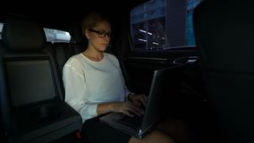 Busy woman typing her speech on laptop, driving to business meeting in taxi. Stock footage stock footage