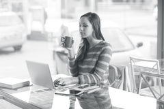 Busy woman working with her laptop. Busy young woman working with her laptop on a desk Royalty Free Stock Photography