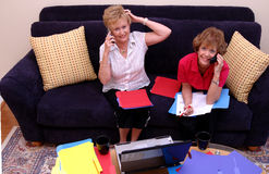 Busy women working at home. Two busy and stressed mature women working from home in a living room Royalty Free Stock Photography