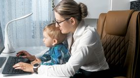 Young busy woman working in office with her toddler boy. Busy women working in office with her toddler boy Stock Image