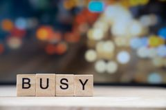 busy word Written In Wooden Cube on wood table with traffic bokeh in background stock photo