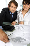 Busy at work. Business couple is making an analyses looking at graphics royalty free stock photos