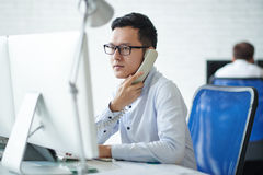 Busy with work. Serious businessman reading something on computer screen and calling on phone Stock Image