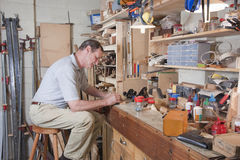 Busy at workbench. Man working at home workbench surrounded by equipment Royalty Free Stock Photo