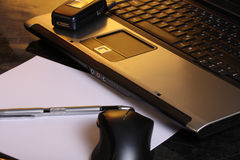 Busy working day. Laptop with cell phone,paper and pen royalty free stock photos