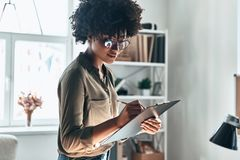 Busy working day. Attractive young African woman writing something down while working in the office royalty free stock images