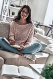 Busy working day. Beautiful young woman in eyewear studying and smiling while sitting on the sofa at home stock image
