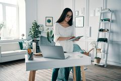 Busy working day. Beautiful young woman using digital tablet while working in home office royalty free stock image