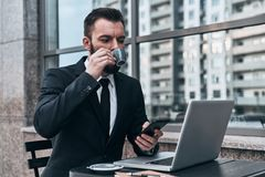 Busy working day. Good looking young man in full suit drinking coffee while sitting in the cafe outdoors royalty free stock image