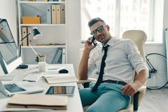 Busy working day. Good looking young man talking on the phone and smiling while sitting in the office royalty free stock photo