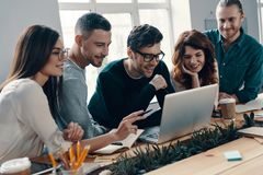Busy working day. Group of young modern people in smart casual wear using modern technologies while working in the creative office royalty free stock image