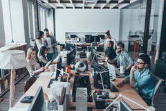 Busy working day in office. Group of young business people in smart casual wear working and communicating while sitting at the large desk in the office together Royalty Free Stock Photos