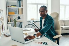 Busy working day. Thoughtful young African man in shirt using laptop while sitting in the office stock image
