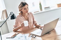 Busy working day. Top view of beautiful young woman in smart casual wear holding a cup of coffee and using laptop while sitting in modern office stock image