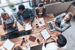 Busy working day. Top view of young modern people in smart casual wear discussing business while working in the creative office royalty free stock images