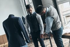 Busy working day. Young fashionable designer measuring client?s sleeve while standing in his workshop stock image