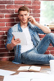 Busy working at home. Handsome young man talking on the mobile phone and looking at his digital tablet while sitting on the hardwood floor at his apartment Stock Photo