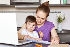 Busy working mother sits in front of opened laptop computer, tries to conecntrate on work, sits against kitchen interior with chil. D, being on maternity leave stock image