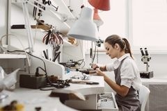 Busy working. Side view of young female jeweler working on a new jewelry product at her workbench. Jewelry making. Busy working. e view of young female jeweler royalty free stock photo