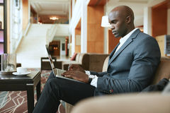 Busy young businessman working on laptop in lobby. Image of busy young businessman working on laptop. African businessman sitting in hotel lobby waiting for stock photography