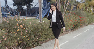 Busy young businesswoman walking along a street Stock Image