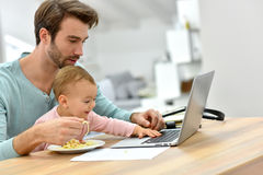 Busy young father feeding baby and working on laptop Stock Photo