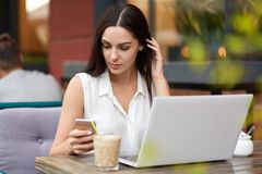 Busy young female freelancer with dark hair works on laptop computer, recieves message on smart phone, types feedback, drinks coff. Ee or cappucino in outdoor stock images