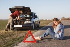 Busy young male driver tries to solve problem with damage engine of car, stands in front of opened hood while his girlfriend sit o royalty free stock image
