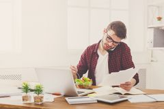 Busy young man has business lunch in modern office interior. Busy at work. Man has business lunch in office, talking on mobile and reading papers. Overworking Stock Images
