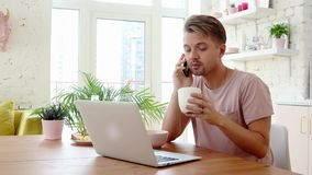 Busy young man having breakfast and using his laptop and smartphone