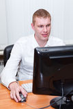 Busy young man in white shirt sitting at pc computer Royalty Free Stock Photo