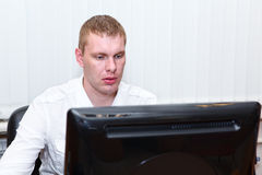 Busy young man in white shirt working at pc Royalty Free Stock Photos