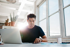 Busy young man working in office Stock Photo