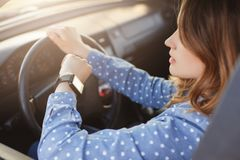 Busy young woman drives car and looks at watch, stuck in traffic jam, hurries to work, being nervous and stressed, feels impatient. Keeps hands on wheel stock images