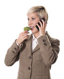 Busy young woman eats healthy while talking on phone. Businesswoman eats broccoli and talks on the phone isolated on white background Royalty Free Stock Image