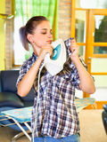 Busy young woman ironing his clothes on self. Stock Photos