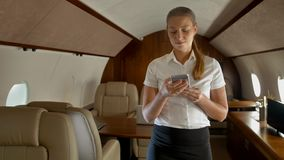 Busy young woman texting in smartphone in business jet. stock video footage