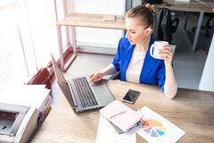 Busy and young woman is wokring. She is using laptop for work. Also girl is drinking tea from white cup. Young woman is. Sitting in office Royalty Free Stock Photography