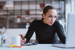 Busy young woman working at her desk Stock Photography
