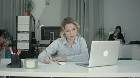 Busy young woman working on the laptop in the office while her coworker using tablet stock footage