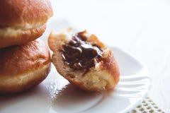 Butées toriques avec du chocolat remplissant du plat blanc, fond en bois blanc image stock